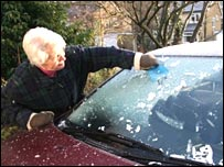 Image of a woman scraping ice from her car