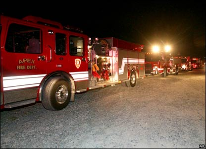 Firefighters and fire trucks line up