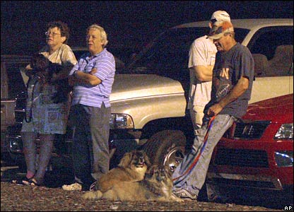 Residents stand outside a shelter at Olive Chapel school in Apex