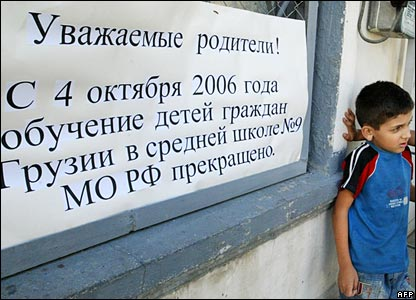 Georgian child outside Russian-run school in Tbilisi, where signs says Georgian children can no longer be taught there
