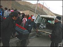 Un grupo de mineros carga el féretro de un compañero.