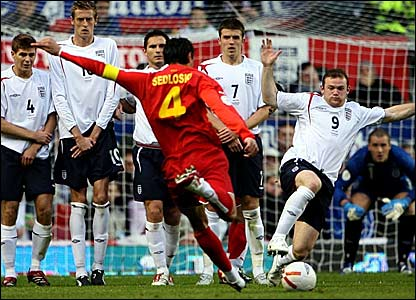 Wayne Rooney (right) charges down a Macedonia free-kick