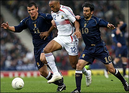 Scotland's Lee McCulloch (left) and Paul Hartley (right) tussle with Thierry Henry