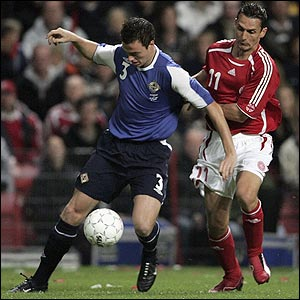 Jonathan Evans in possession for Northern Ireland against Peter Lovenkrands
