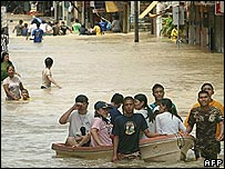 People are transported in a boat as others tread through the floodwaters on the main street in Angthong province north of Bangkok, 08 October 2006