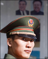 A Chinese paramilitary officer walks past the portraits of North Korean leader Kim Jong-il and his late father Kim Il-sung outside the North Korean embassy in Beijing