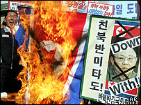 South Korean protesters burn a defaced North Korean flag during a rally denouncing North Korea's nuclear test