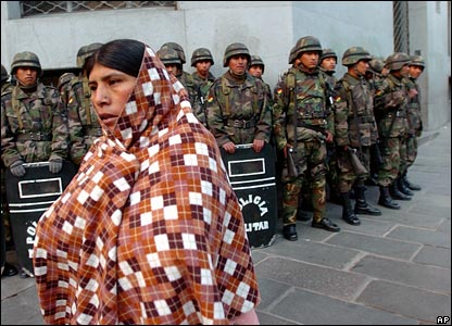 A woman walks past Bolivian soldiers