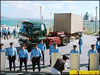 Japanese riot police officers stand guard as a trailor loaded with a container believed to be carrying Patriot missiles leaves a port in Japan 11/10/2006