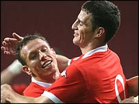 Jason Koumas (right) celebrates his goal with Wales captain Craig Bellamy
