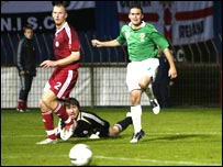David Healy watches the ball on its way to the Latvian net