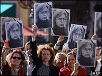 Supporters hold up placards showing Anna Politkovskaya during Vladimir Putin's visit to Germany