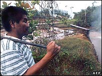 Peruvian man looks at pipe feed into the Amazon river