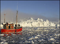 A trawler passes icebergs in Greenland