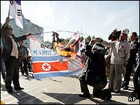 South Korean protesters burn a defaced North Korean flag during a rally denouncing North Korea's nuclear test in Seoul