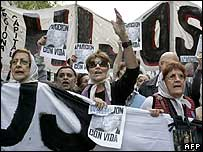 """Members of Argentine's human rights civil association """"Madres de Plaza de Mayo"""" hold banners with the portrait of Julio Lopez"""