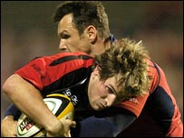 Edinburgh's Phil Godman is tackled by Trevor Halstead