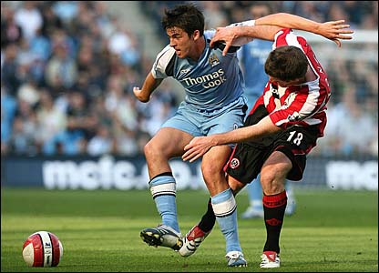 Joey Barton shields the ball from Michael Tonge