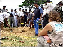 An Action Against Hunger worker watches two of the 17 aid workers' bodies being exhumed in September 2006
