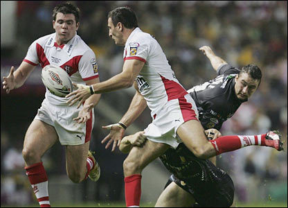 Lee Gilmour (C) of St. Helens offloads to teammate Jamie Lyon