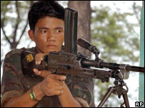 A Maoist rebel stands guard as other rebels train in a photo from July 2006