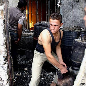 Iraqi man moves gas cylinder after bombing in Kirkuk, 15 October 2006