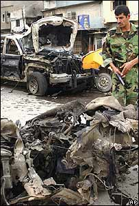 Iraqi soldier inspects wreckage after bombings in Kirkuk, 15 October 2006