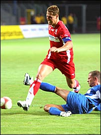 Michael Schumacher is tackled by German actor Til Schweiger in a charity match