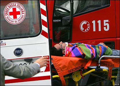 An injured man on a stretcher is placed in an ambulance