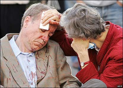An injured woman wipes blood from an injured man's face
