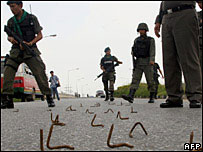 Thai soldiers clear nails from the road left by suspected insurgents in Yala province on 17 October 2006