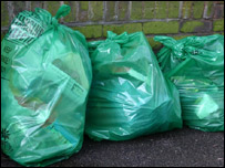 Green rubbish bags left against a wall