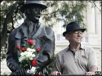 Un hombre posa junto a estatua de Imre Nagy