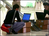 Man sits in front of laptop on shopping mall