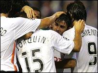 Valencia's David Villa is mobbed by his team-mates after scoring against Shakhtar