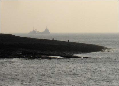 Two fishermen look on as a ship appears out of the mist off Sully Island (John Parker)