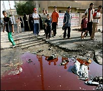 Iraqis stand around a pool of blood following an insurgent attack