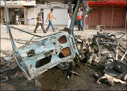 Iraqis pass a car bomb wreck in Baghdad