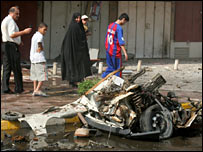 Iraqis walk past a car bomb wreck in Baghdad