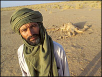 Man with dead camel in desert. Image: Jim Loring/Tearfund