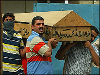 Iraqis carry a body from morgue in Baghdad