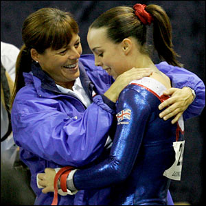 Beth celebrates with her coach after performing on the horizontal bar