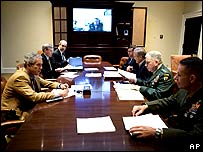 President Bush speaks with Vice-President Dick Cheney, on screen, and military commanders