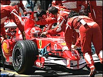 Ferrari mechanics try to fix Schumacher's car but to no avail