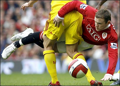 "Wayne Rooney (C) fights for the ball against Liverpool""s Xabi Alonso and falls"