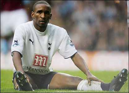 Jemain Defoe sits on the pitch and looks on after missing a chance on goal
