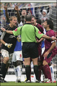 Jussi Jaaskelainen (L), Kevin Nolan (C) and Ivan Campo (R) of Bolton Wanderers argue with referee, Mike Dean after he awards a second penalty to Blackburn