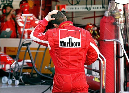 Schumacher returns to the Ferrari pits after retirement in Japan