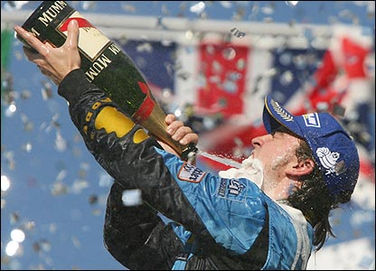 Alonso celebrates winning the title with a bottle of champagne
