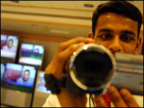 A man with a camera in front of news channels